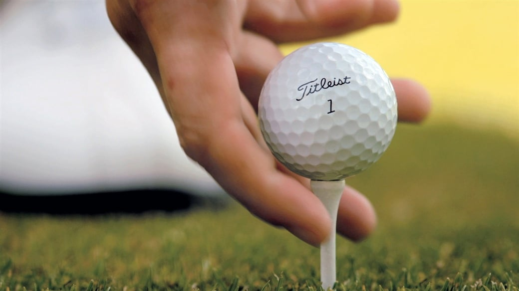 Player tees up a Pro V1 golf ball