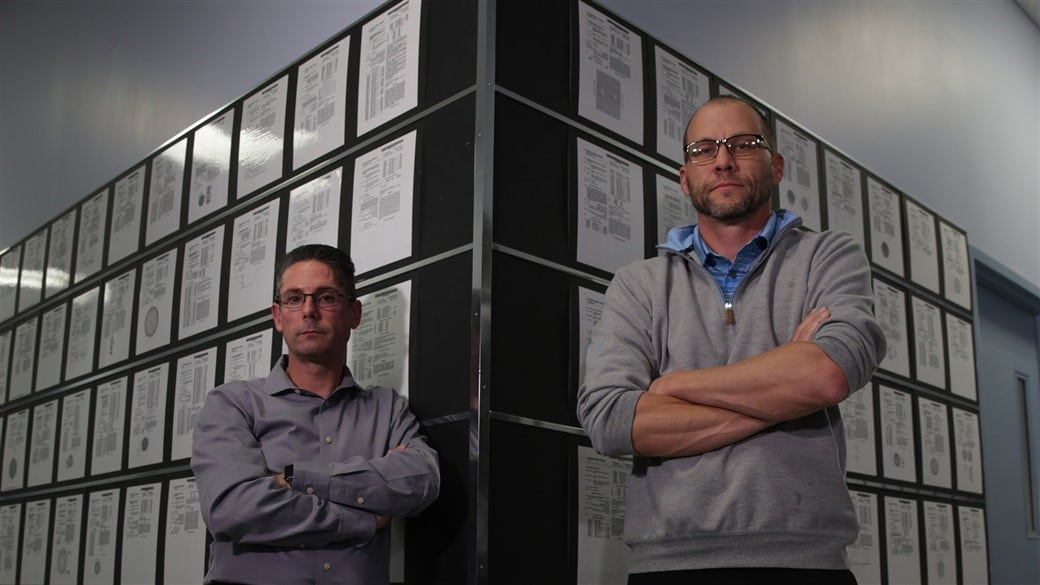 Brian Comeau and Derek Ladd stand in front of Titleist patents in Golf Ball R&D