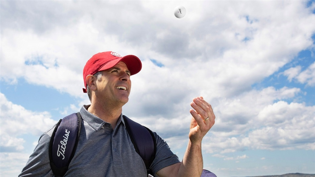 Amateur golfer tosses a new Titleist TruFeel golf ball in the air